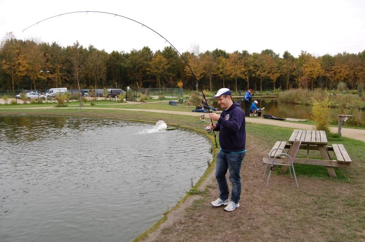 Fighting a big fish in a fishing pond