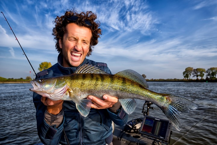 Happy fisherman with a zander